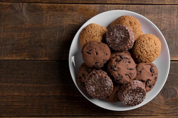 茶色の木製テーブルの皿にさまざまなおいしいクッキー。碑文のためのスペースと上面図