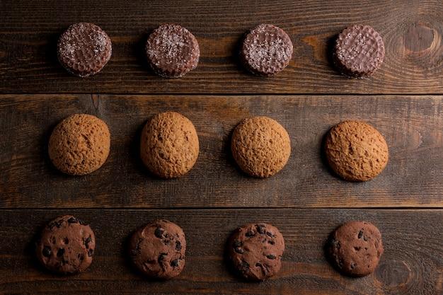 茶色の木製テーブルにさまざまなおいしいクッキーが一列に積み上げられています。上からの眺め
