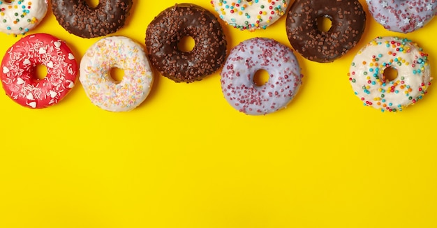 Different tasty donuts on yellow background, top view