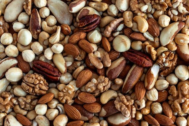 ヒープ内のさまざまなおいしいナッツ。ナッツの背景。クルミ、ピーカン、アーモンド、ヘーゼルナッツ、マカダミア、カシューナッツ