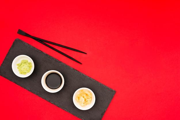 Различные вкусные соусы с маринованным имбирем в мисках и палочками на черном камне над красным столом