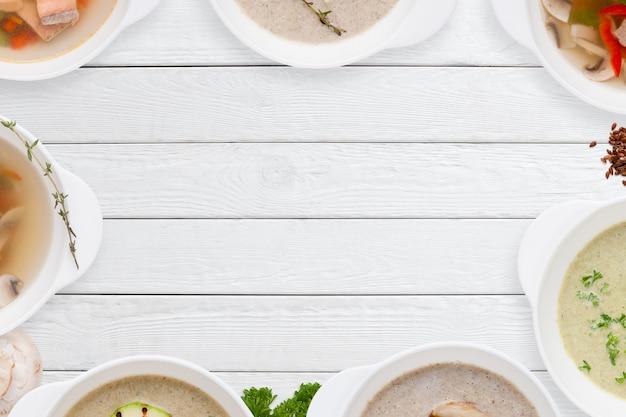 白い木製のテーブルの上のさまざまなおいしいスープフレーム