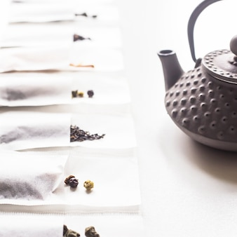Different teas in a disposable filter bags for brewing next to a gray cast iron kettle on a white background
