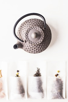 Different teas in a disposable filter bags for brewing next to a gray cast iron kettle on a white background.