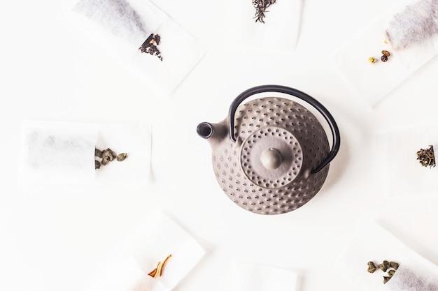 Различные чаи в одноразовых фильтровальных пакетиках для заваривания рядом с серым чугунным чайником