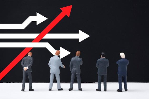異なる考え方とビジネスとテクノロジーの混乱の概念。ビジネスマンが立って、黒板に白い矢印が付いている赤い矢印を検討してください。