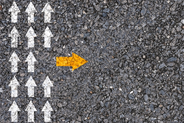 Различное мышление и концепция разрушения бизнеса и технологий. желтая стрелка вне направления линии с белой стрелкой на дорожном асфальте.