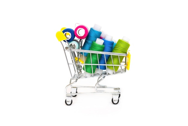 Different threads are in a small shopping cart. blue purple yellow, green, colors.