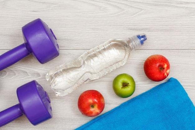 회색 바닥에 있는 방이나 체육관에 물과 사과 한 병을 갖춘 피트니스를 위한 다양한 도구