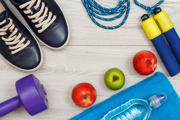 회색 바닥에 있는 방이나 체육관에 물 한 병과 사과가 있는 피트니스를 위한 다양한 도구