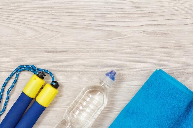 회색 바닥에 있는 체육관이나 방에 물 한 병이 있는 피트니스를 위한 다양한 도구