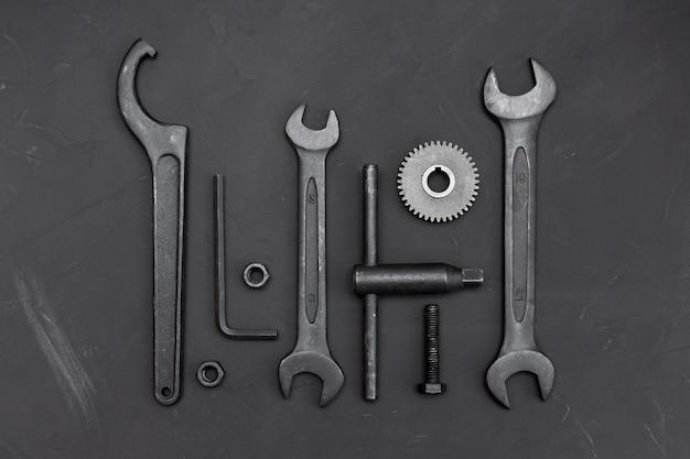 暗いテーブル上のさまざまなツール。レンチツール、歯車、リングスパナ、モンキーレンチ、歯車、ネジ、ボルト。