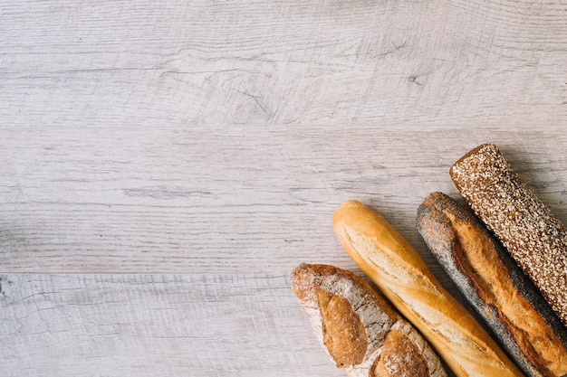 Different type of baguettes on wooden textured background