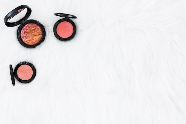 Different type of black pink compact powder on white fur backdrop