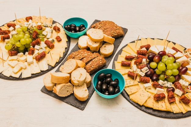Different type of bread slices with olives and platter cheese on wooden desk