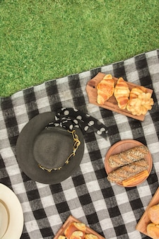 Different type of breads with hat on blanket over the green grass