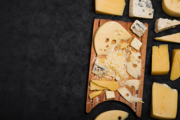 Different type of cheese on black background