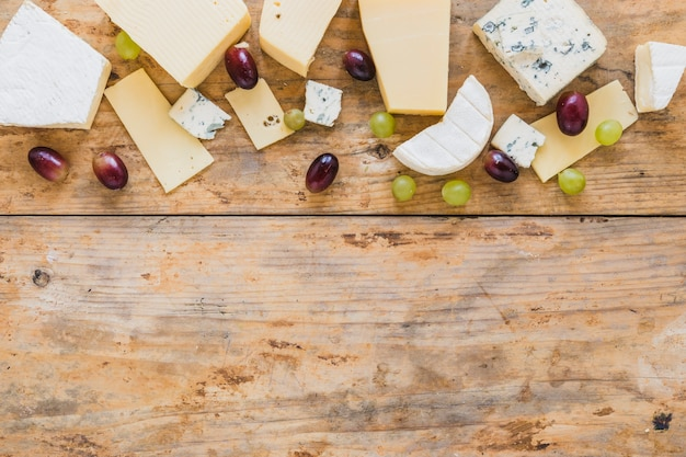 Different type of cheese blocks with grapes on wooden desk