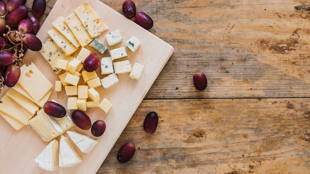Different type of cheese cubes with grapes on wooden desk