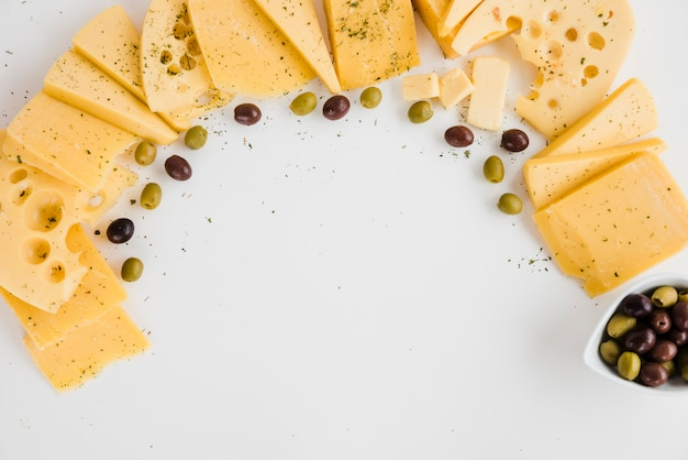 Different type of cheese slices with olives on white backdrop