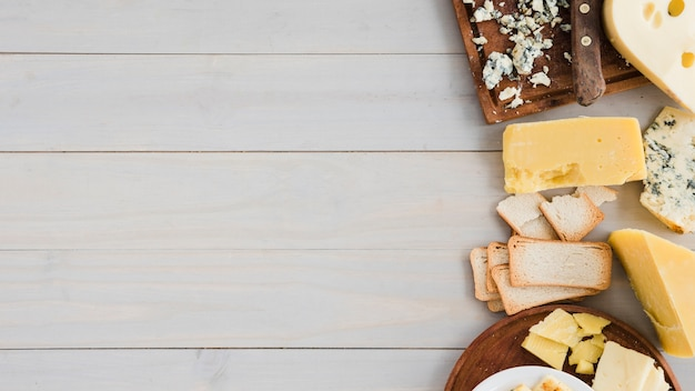 Different type of cheese with bread on wooden table