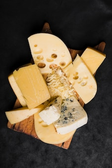 Different type of cheese on wooden board over the black background