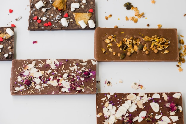 Different type of chocolate bars on white backdrop
