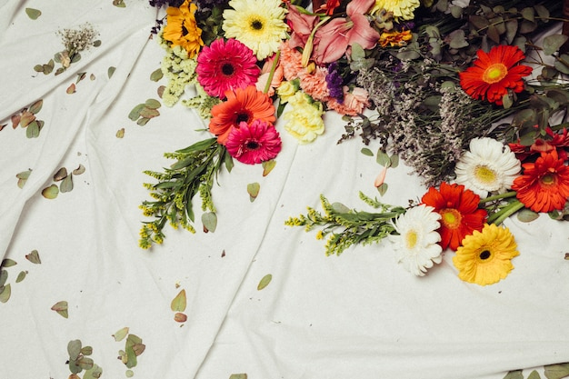 Different type of colorful gerbera flowers and leaves on white cloth