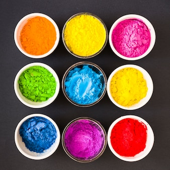 Different type of colorful holi powder in the white and glass bowl on black backdrop