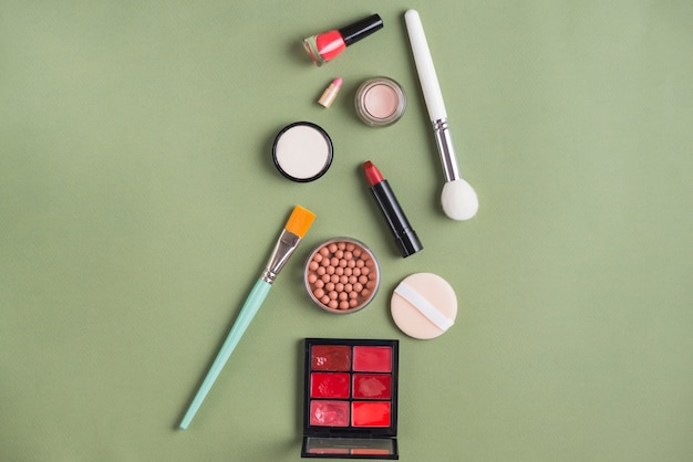 Different type of cosmetic products on green background