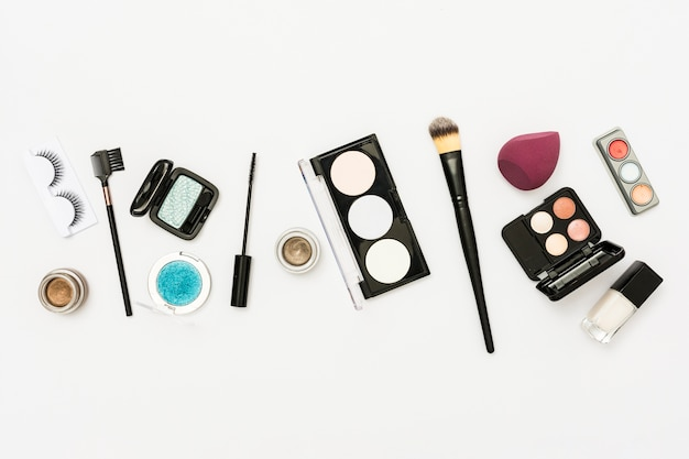 Different type of cosmetics palette with eyeshadow; nail polish bottle and brushes on white backdrop