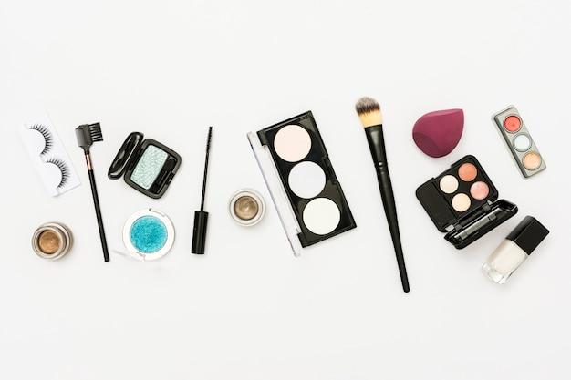 Diversi tipi di tavolozza di cosmetici con ombretto; bottiglia di smalto e pennelli su sfondo bianco