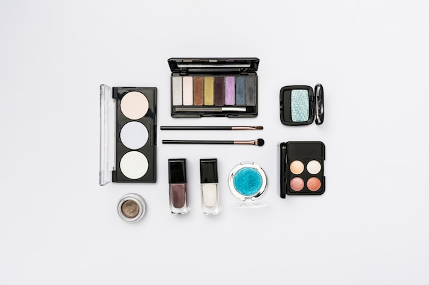 Different type of cosmetics palette with makeup brushes on white background
