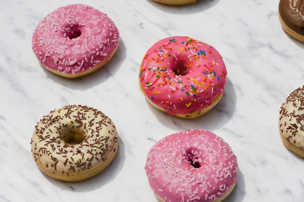Different type of donuts on marble textured backdrop