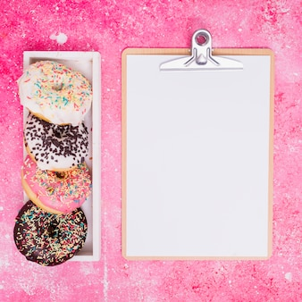 Different type of donuts in white rectangular box near the clipboard with white paper against pink background