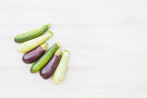 Different type of eggplants on wooden background