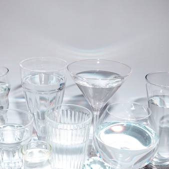 Different type of glasses with liquid against gray backdrop