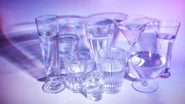 Different type of glasses with liquid on colored backdrop