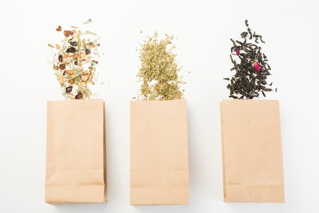 Different type of herbal tea spilling from brown paper bag on white background