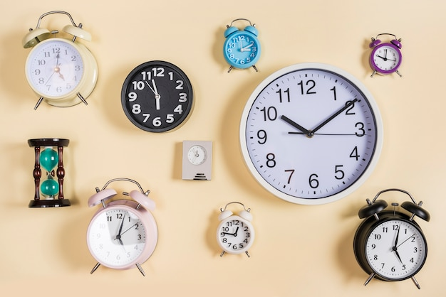 Different type of hour glass; clocks and alarm clocks on beige background
