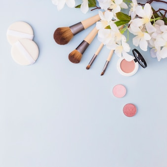Different type of makeup brush; sponge; eye shadow and blusher with white flowers on blue background