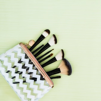 Different type of makeup brushes in transparent design bag on mint green backdrop