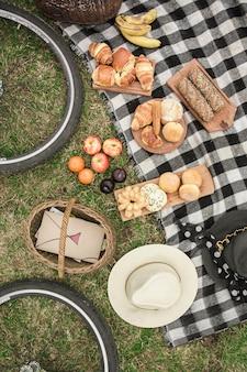 Различные виды хлеба с шляпой и корзиной для пикника на одеяле над зеленой травой Бесплатные Фотографии