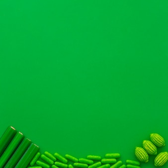 Different type of candies at the bottom of green background