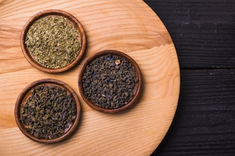 Different type of dried tea leaves on wooden table