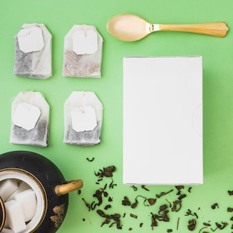 Различные виды травяных пакетиков чая, кубики сахара, ложка и белая коробка на цветном фоне