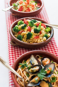 Различные макаронные блюда итальянской кухни, приготовленные на клетчатой салфетке