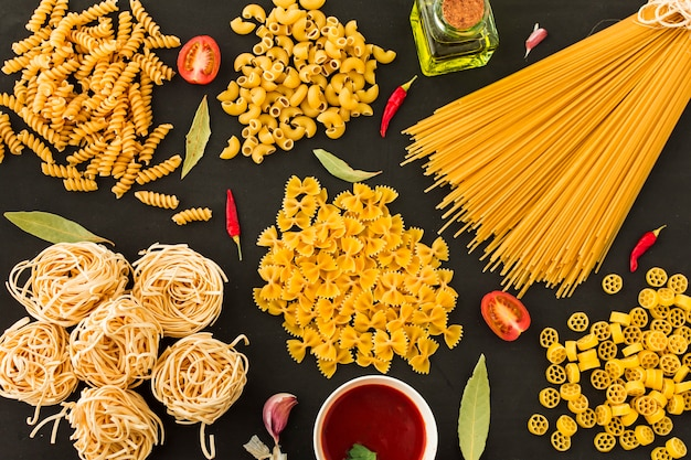 Различные типы сырых макарон с ингредиентами на черном фоне