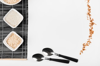 Different type of uncooked rice on placemat with spoon and cinnamon sticks on white background