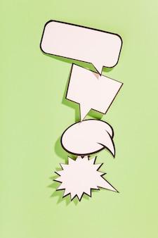 Различные типы белых пузырьков речи на зеленом фоне